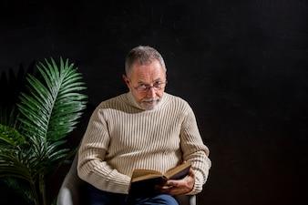 Uomo anziano con il libro che guarda l'obbiettivo