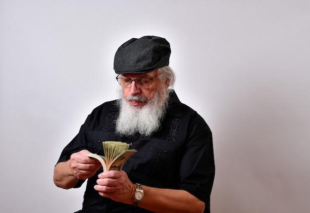 Uomo anziano con la barba che conta i suoi soldi