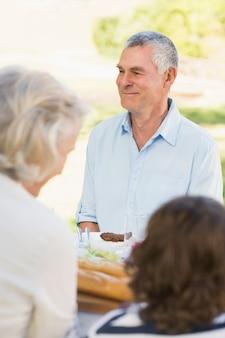 Uomo anziano con la famiglia al tavolo da pranzo all'aperto