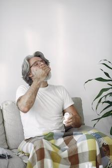 Uomo anziano con le pillole in mano. assistenza sanitaria, trattamento, concetto di invecchiamento.