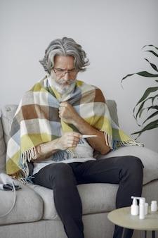 Uomo anziano da solo seduto sul divano. uomo malato coperto di plaid. nonno con termometro.