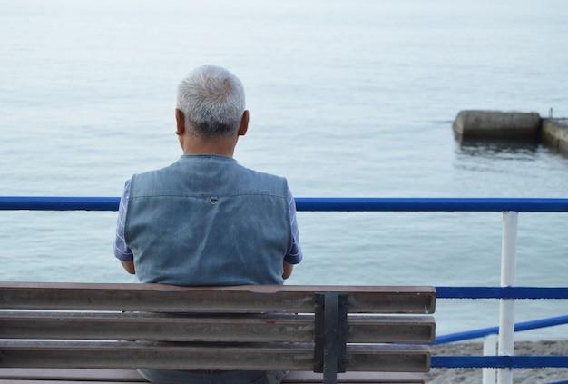 Uomo anziano dai capelli grigi solitario seduto in riva al mare su una panchina, la vista dalla parte posteriore