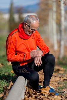 Uomo anziano del corridore che riposa al parco mentre monitorando il suo esercizio