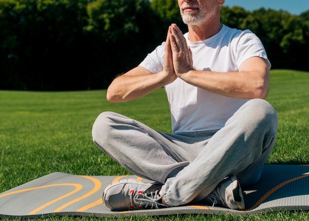 Uomo anziano del primo piano che medita all'aperto