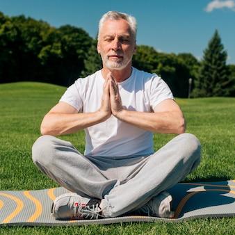 Uomo anziano della foto a figura intera che medita all'aperto