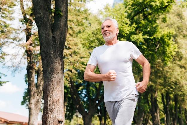 Uomo anziano di angolo basso che corre all'aperto