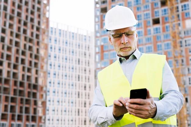 Uomo anziano di angolo basso che esamina smartphone