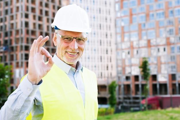 Uomo anziano di smiley con il casco che mostra approvazione
