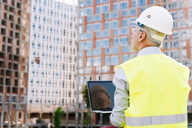 Uomo anziano di vista posteriore con il computer portatile della tenuta del casco