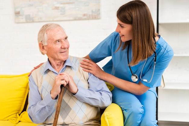 Uomo anziano e badante che si siedono sul sofà giallo