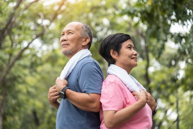 Uomo anziano e donna che si esercitano insieme al parco all'aperto.