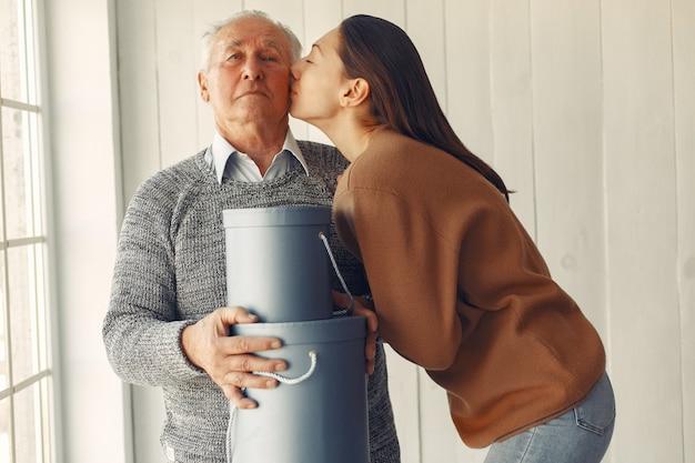 Uomo anziano elegante che sta a casa con sua nipote