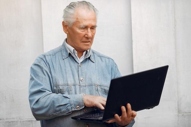 Uomo anziano elegante che sta e che per mezzo di un computer portatile