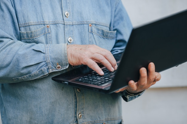 Uomo anziano elegante che sta sul fondo grigio e che per mezzo di un computer portatile