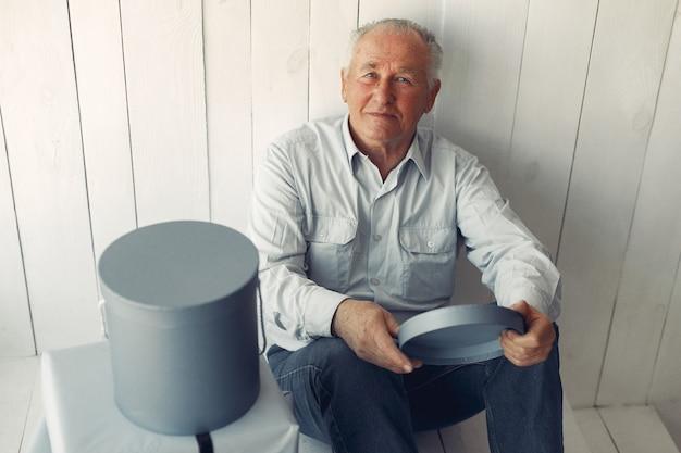 Uomo anziano elegante seduto a casa con regali di natale