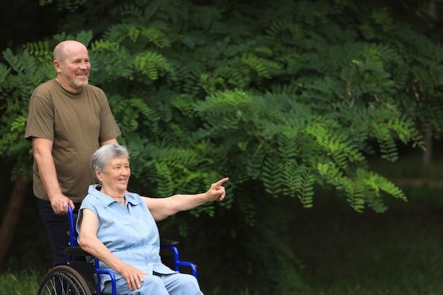 Uomo anziano felice che cammina con donna anziana disabile che si siede in sedia a rotelle all'aperto