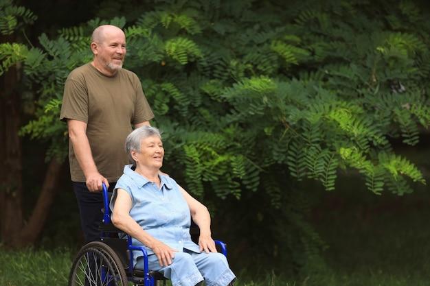 Uomo anziano felice che cammina con donna anziana disabile che si siede in sedia a rotelle