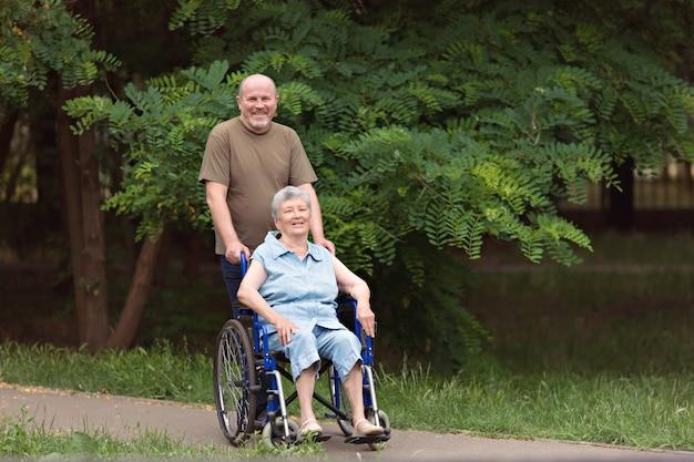 Uomo anziano felice che cammina con donna anziana disabile seduta in sedia a rotelle all'aperto