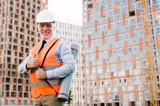Uomo anziano felice di angolo basso che mostra approvazione