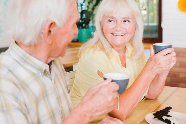 Uomo anziano felice e donna che beve il tè