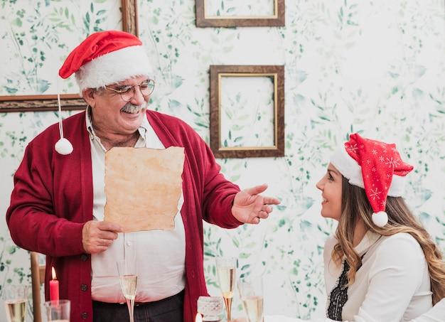 Uomo anziano felice leggendo da carta al tavolo festivo