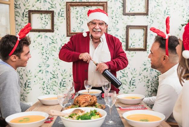 Uomo anziano in cappello di santa apertura bottiglia di vino al tavolo festivo