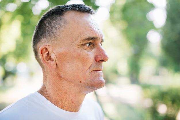 Uomo anziano in maglietta bianca che osserva via