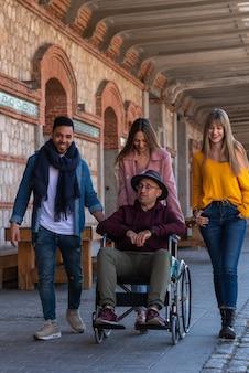 Uomo anziano in sedia a rotelle accompagnato da giovani felici