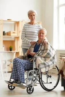 Uomo anziano in sedia a rotelle con moglie