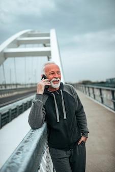 Uomo anziano in tuta sportiva che parla sullo smartphone sul ponte della città.