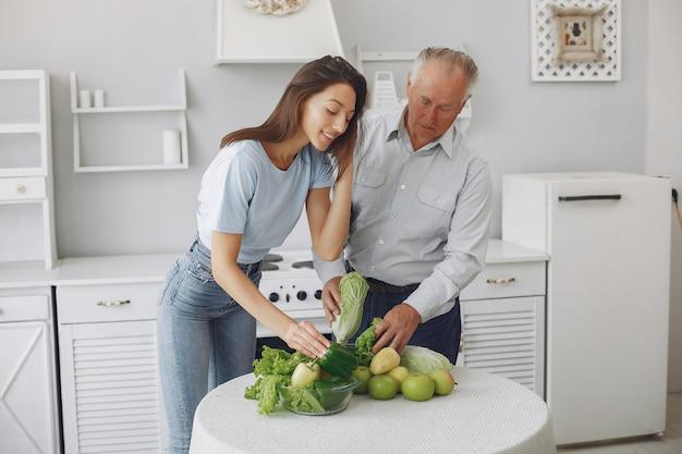 Uomo anziano in una cucina con la giovane nipote