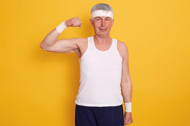 Uomo anziano indoor indossando abbigliamento sportivo e fascia, in piedi con una mano in alto e mostrando il suo bicipite, fotografato dopo aver fatto esercizi fisici. concetto di stile di vita sano.