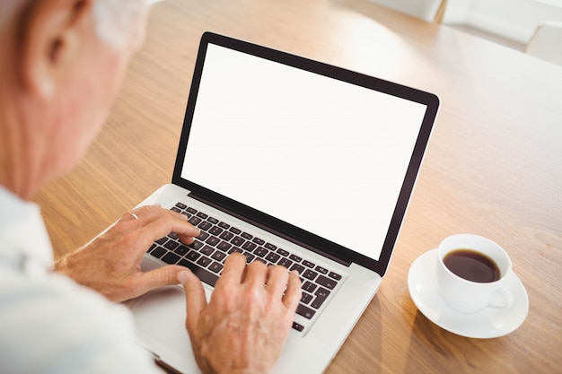 Uomo anziano messo a fuoco che scrive sul computer portatile a casa