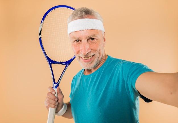 Uomo anziano moderno con la racchetta da tennis