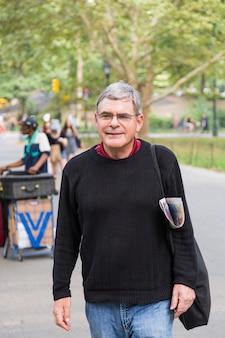 Uomo anziano pensionato al parco, a piedi e rilassante, espressione sorridente