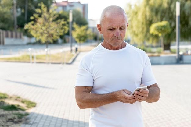 Uomo anziano più anziano cheking il suo telefono