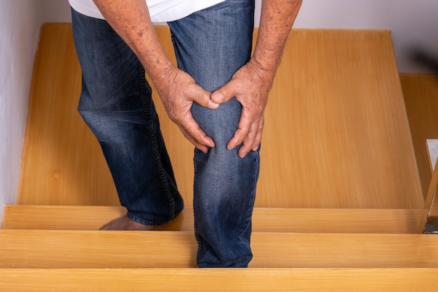 Uomo anziano salendo le scale a casa e toccando il ginocchio dal dolore dell'artrite