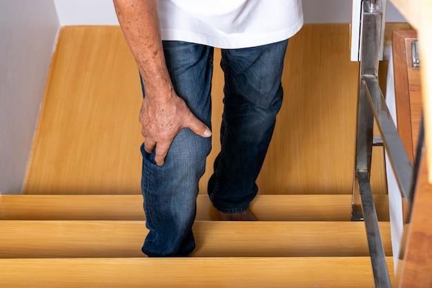 Uomo anziano salendo le scale e toccando il ginocchio per il dolore dell'artrite. assistenza sanitaria. giornata mondiale degli anziani.