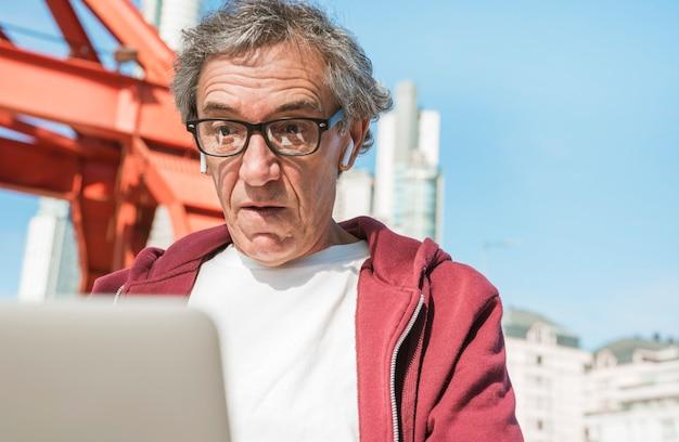 Uomo anziano scosso che indossa gli occhiali neri che esaminano computer portatile