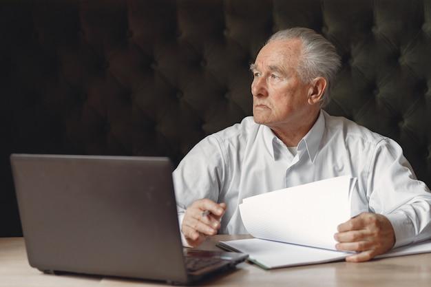 Uomo anziano seduto al tavolo e lavorare con un computer portatile