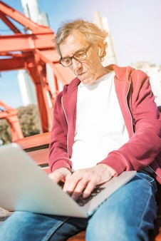Uomo anziano seduto sulla panchina digitando sul computer portatile all'aperto