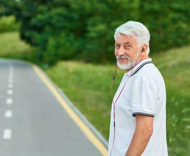 Uomo anziano sorridente che sta sulla pista della città che esamina macchina fotografica.