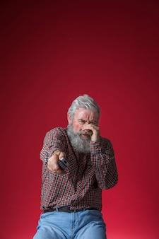 Uomo anziano spaventato guardando film horror in tv tenendo in mano il telecomando su sfondo rosso
