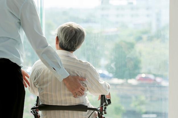 Uomo anziano su sedia a rotelle e medico in ospedale sanità e concetto medico per commerciale