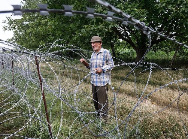 Uomo anziano su supporto locale vicino al filo spinato sulla linea di separazione con la regione occupata di tskhinvali confine de facto della georgia con la sua regione separatista dell'ossezia meridionale