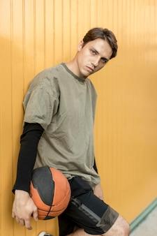 Uomo appoggiato a un muro con il basket