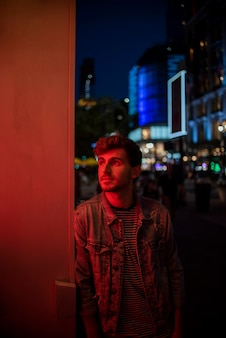 Uomo appoggiato a un muro e guardando lontano