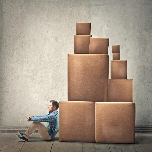 Uomo appoggiato a una pila di scatole