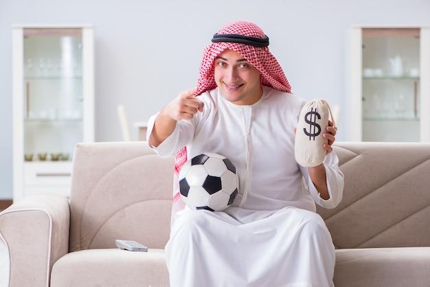 Uomo arabo che guarda il calcio di sport alla tv