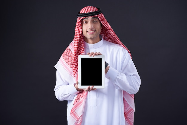 Uomo arabo che posa con la compressa nera isolata.